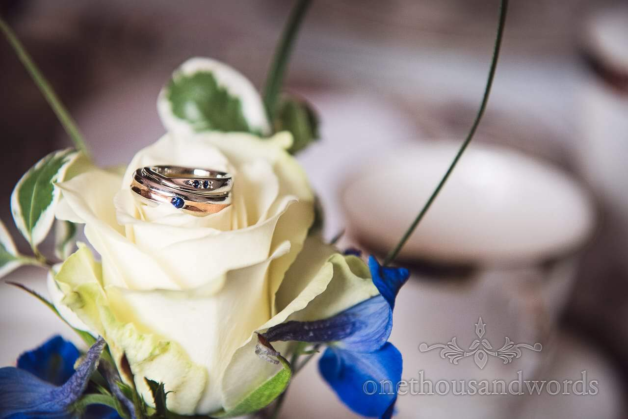 Bride and groom's wedding rings with blue gemstones on white rose