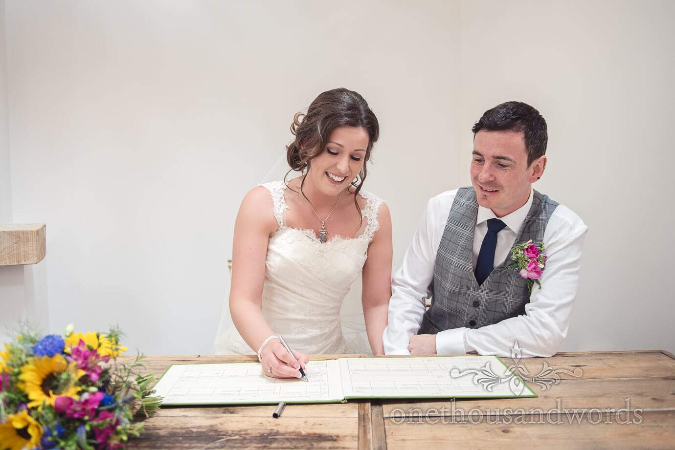 Bride and groom sign marriage register on wooden table at The Old Vicarage Wedding