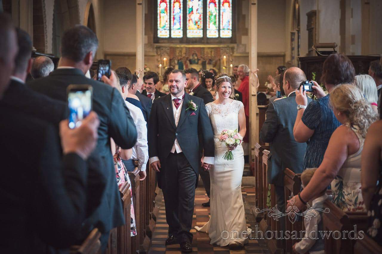 Bride and groom walk down the aisle together in Dorset church wedding ceremony
