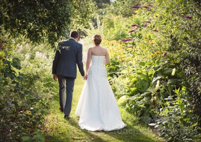 Bride and groom walk into flower garden at Upton House wedding venue