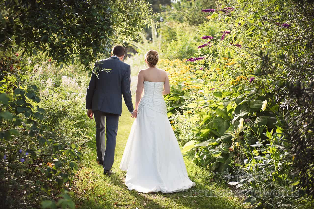 Bride and groom walk into flower garden at Upton House wedding venue