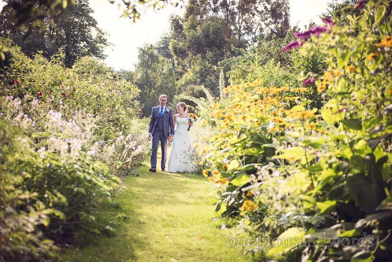 Bride and groom walk through flower garden at Upton House wedding venue in Dorset