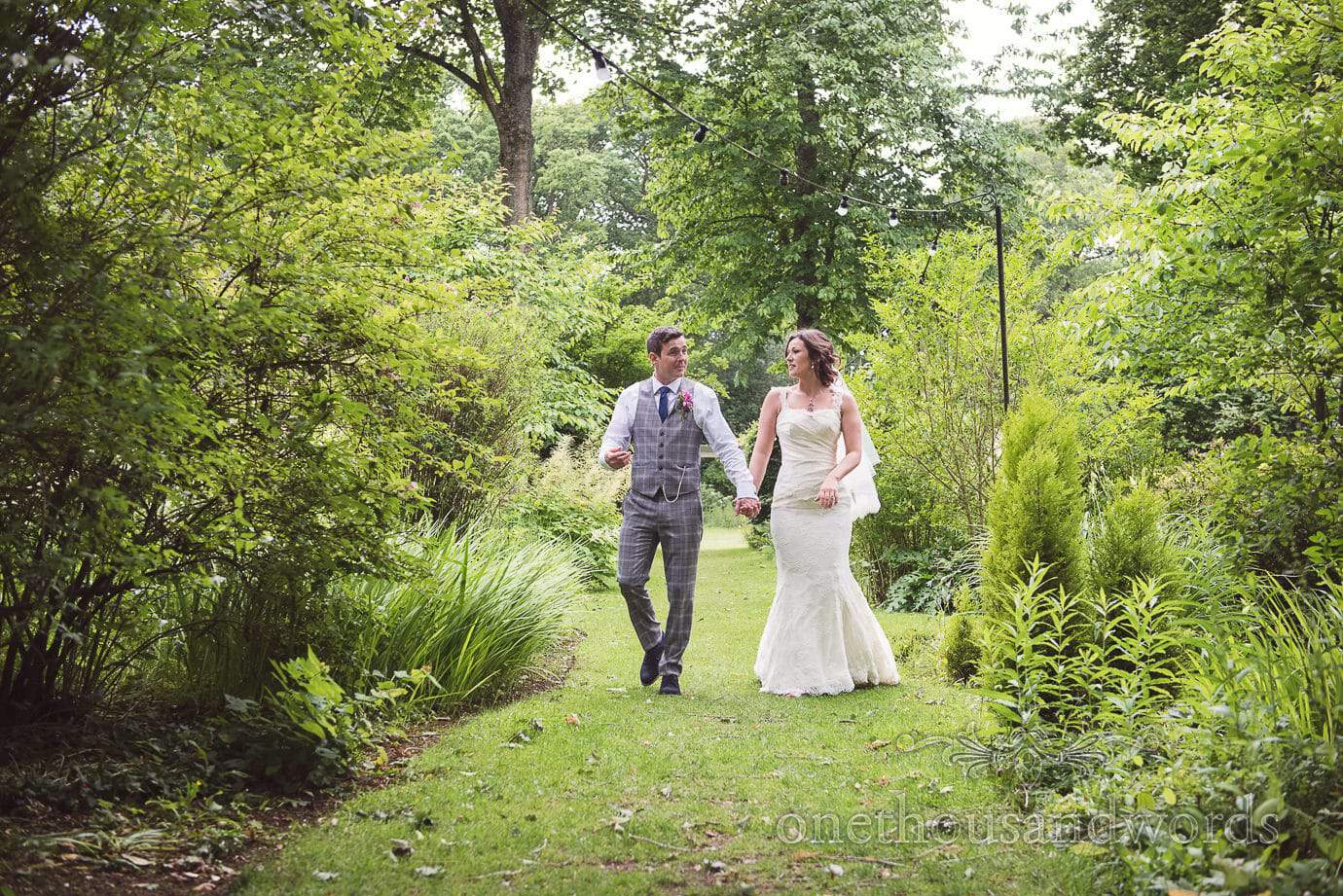 Bride and groom walk through gardens at The Old Vicarage Wedding venue in New Forest