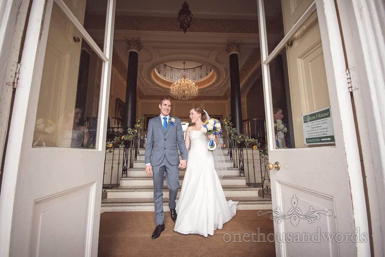Bride and groom walk through main doorway at Upton House wedding venue in Dorset