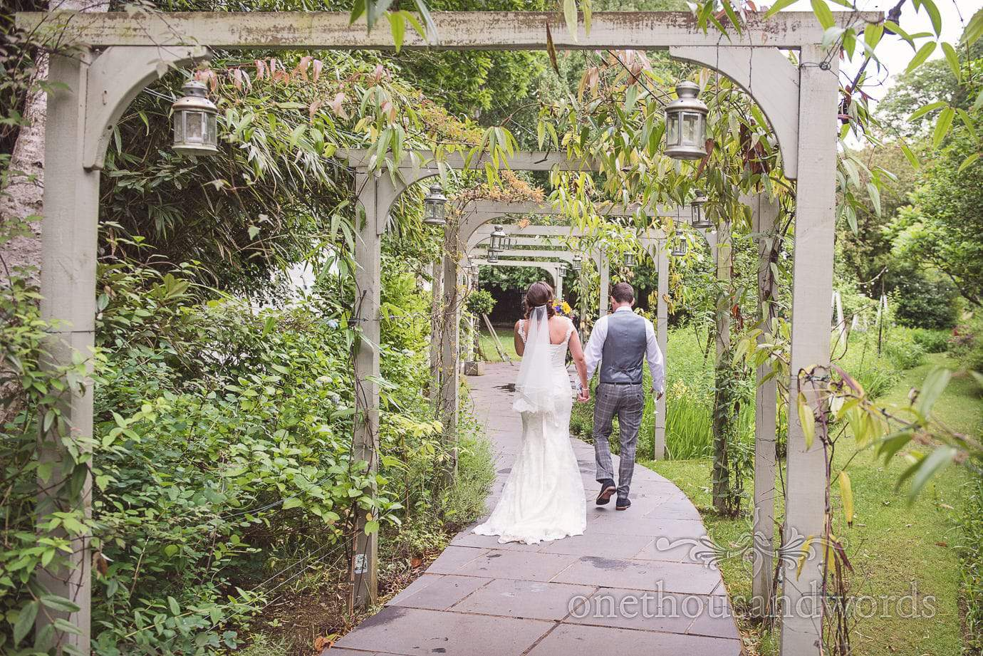Bride and groom walk through wooden archways in The Old Vicarage wedding gardens