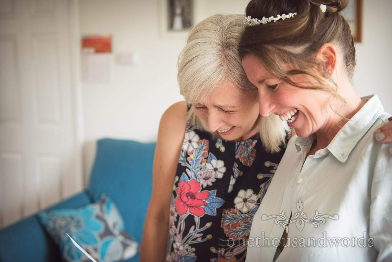 Bride and sister laugh at wedding morning card during bridal preparations