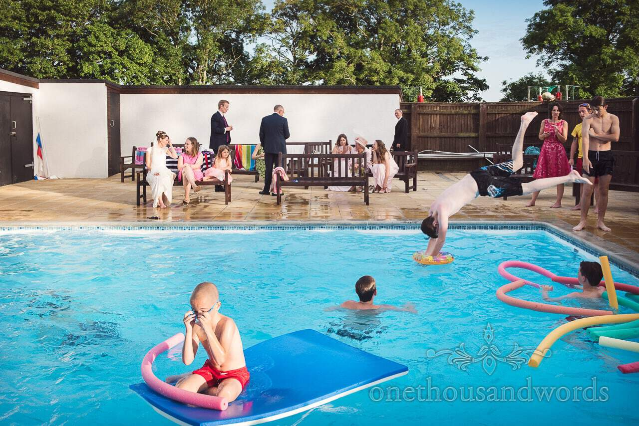 Bride and wedding guests at swimming pool at Castle Court School wedding