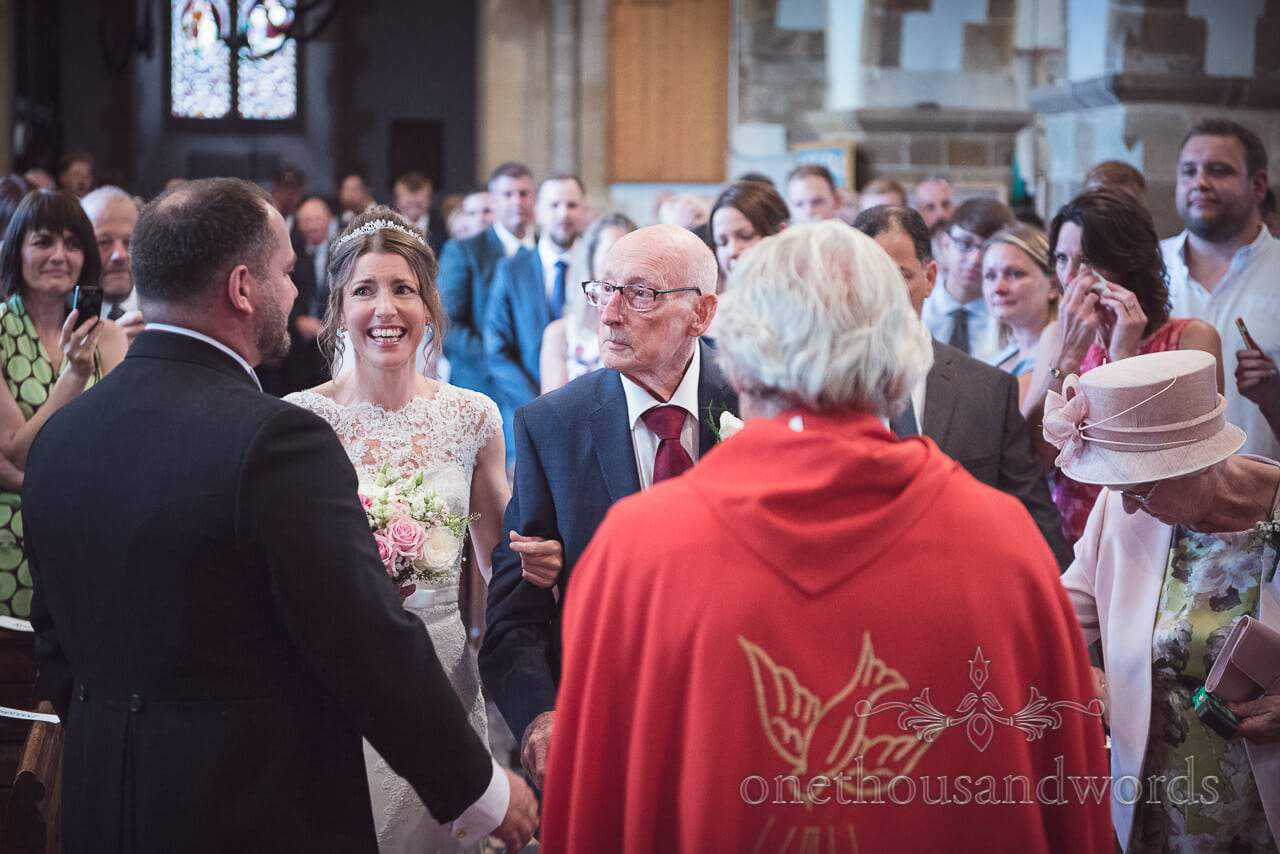 Bride arrives at alter with father at Church of England wedding ceremony in Dorset