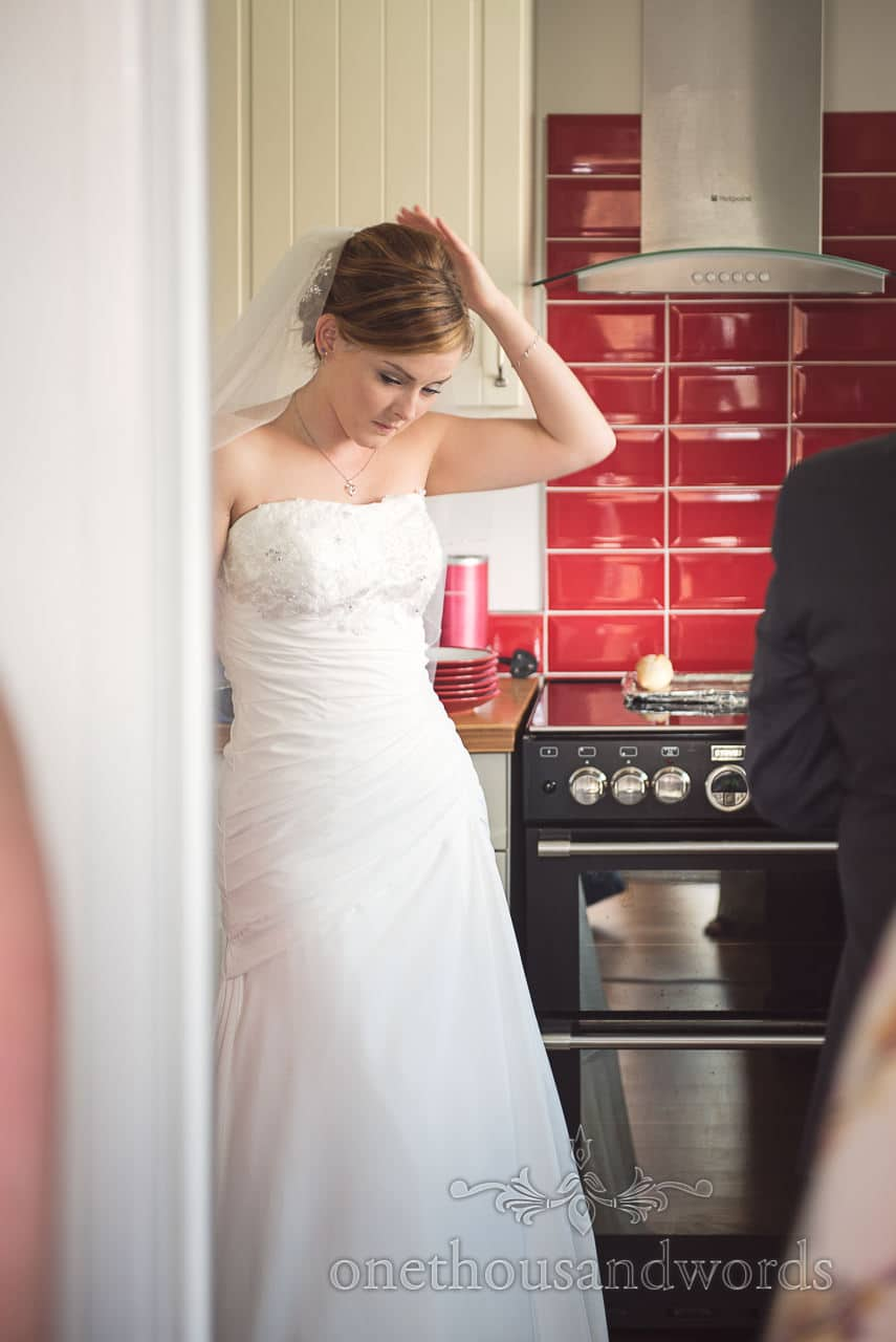 Bride checks veil as she waits in red tiled kitchen on wedding morning in Poole