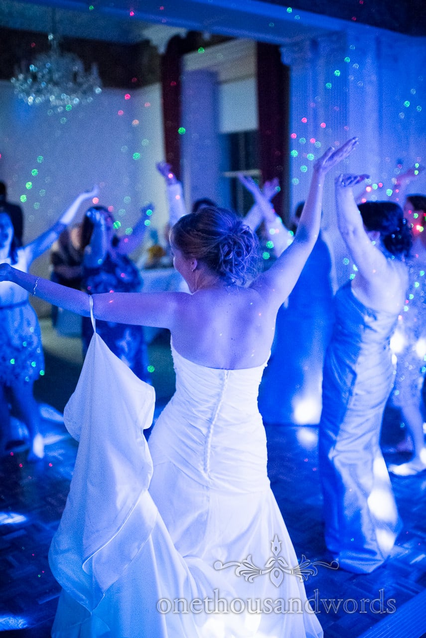Bride dancing in blue disco lights at Upton House wedding venue in Dorset