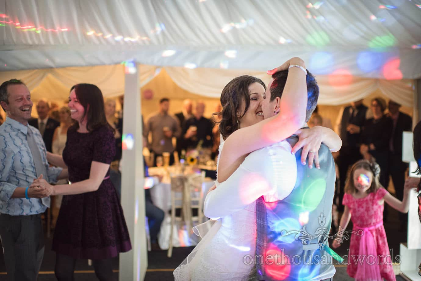 Bride embraces groom on wedding marquee dance floor at The Old Vicarage Wedding