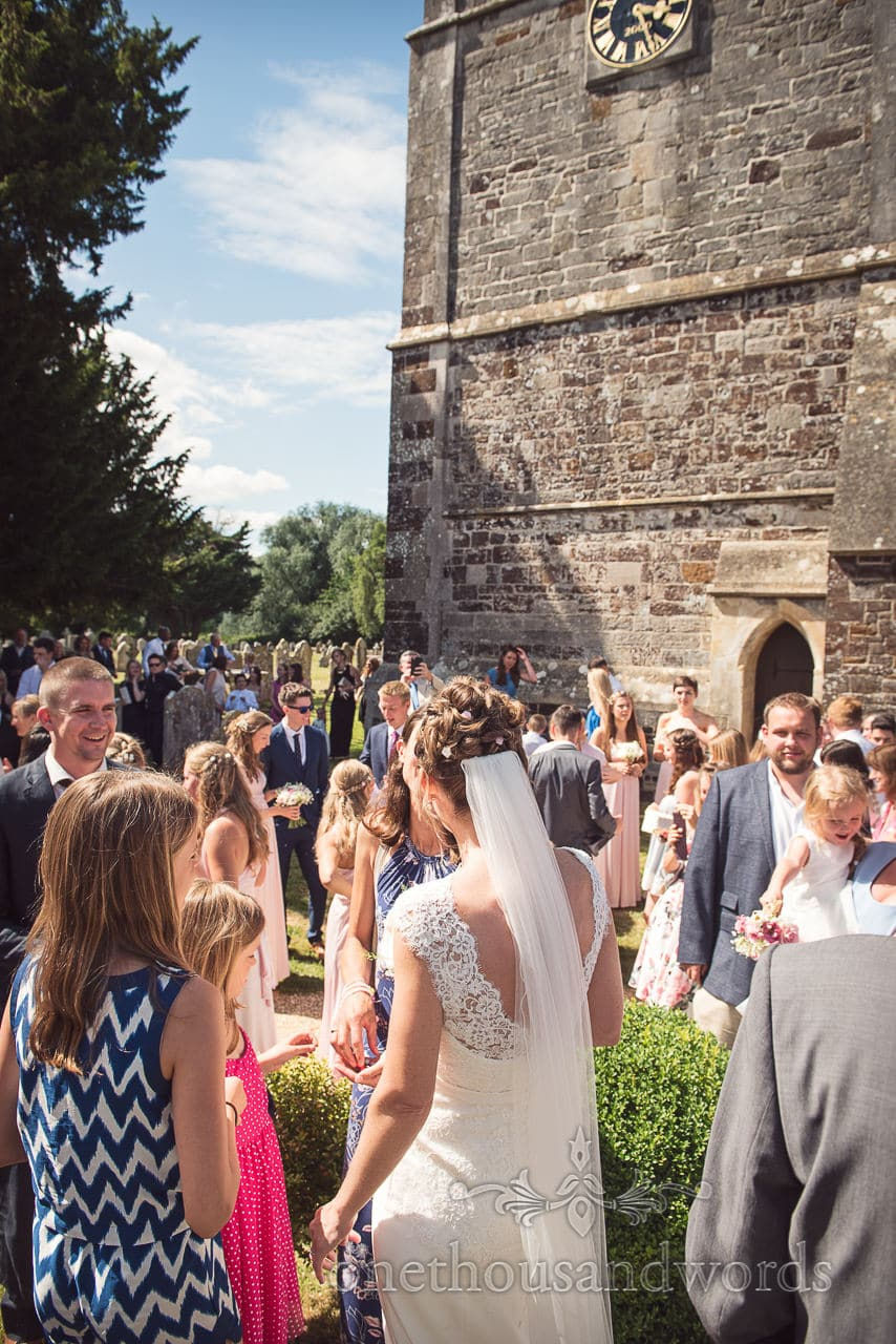 Bride greets wedding guests outside Dorset stone countryside church wedding venue