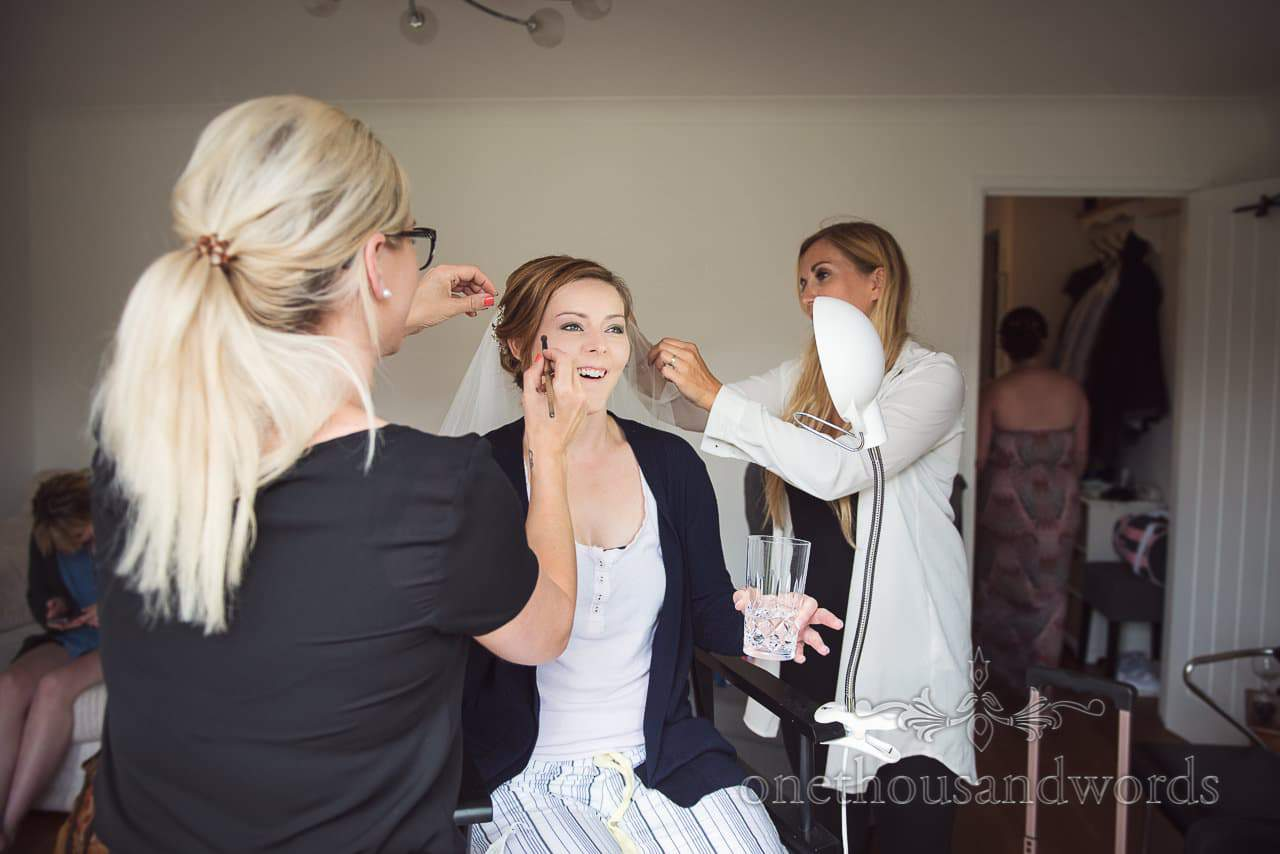 Bride has wedding hair and make up styled at the same time on wedding morning in Dorset