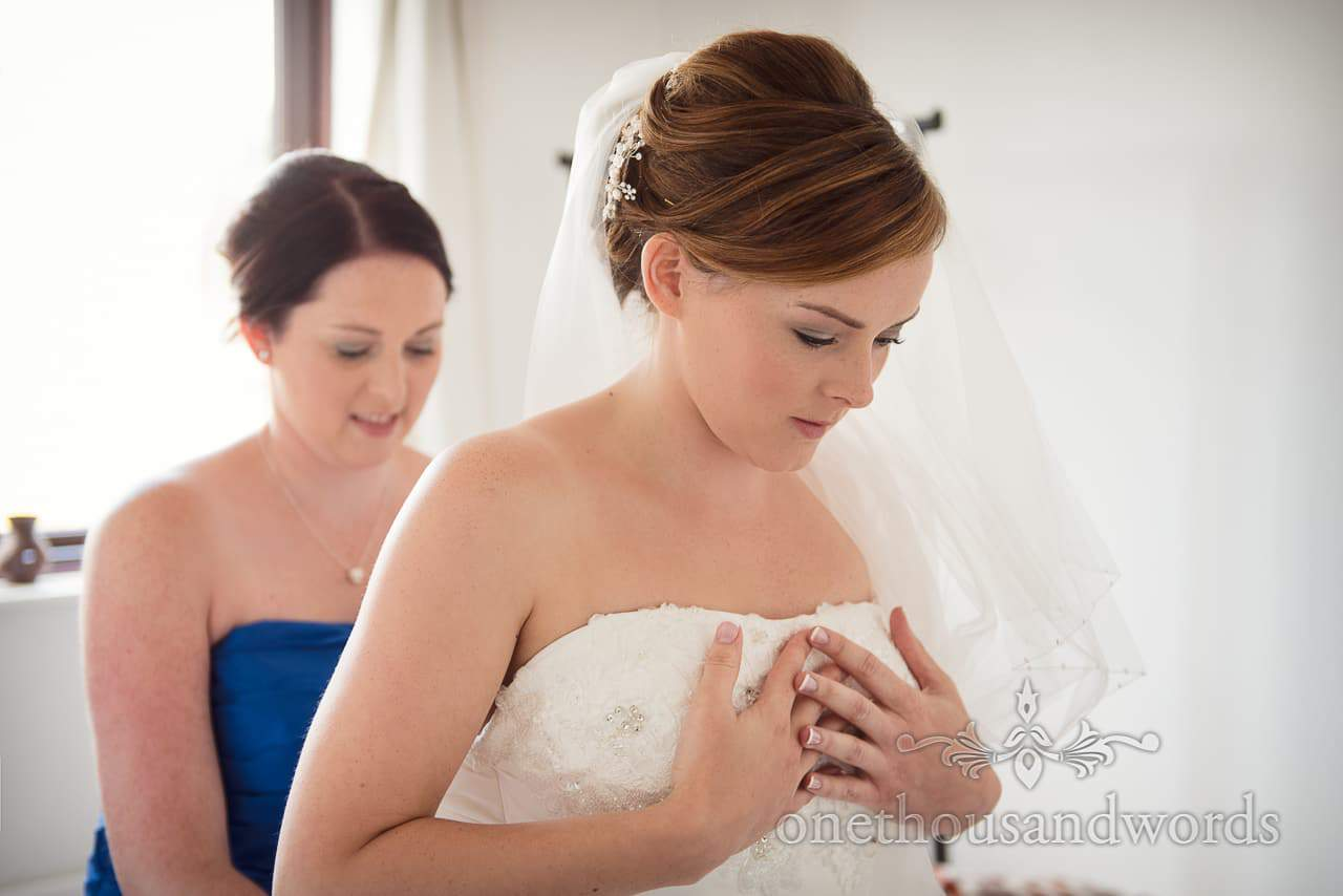 Bride holds chest as she is laced into her white wedding dress on wedding morning