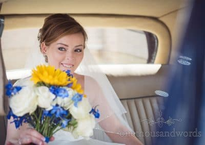 Bride in classic Daimler wedding car with blue, yellow and white bouquet