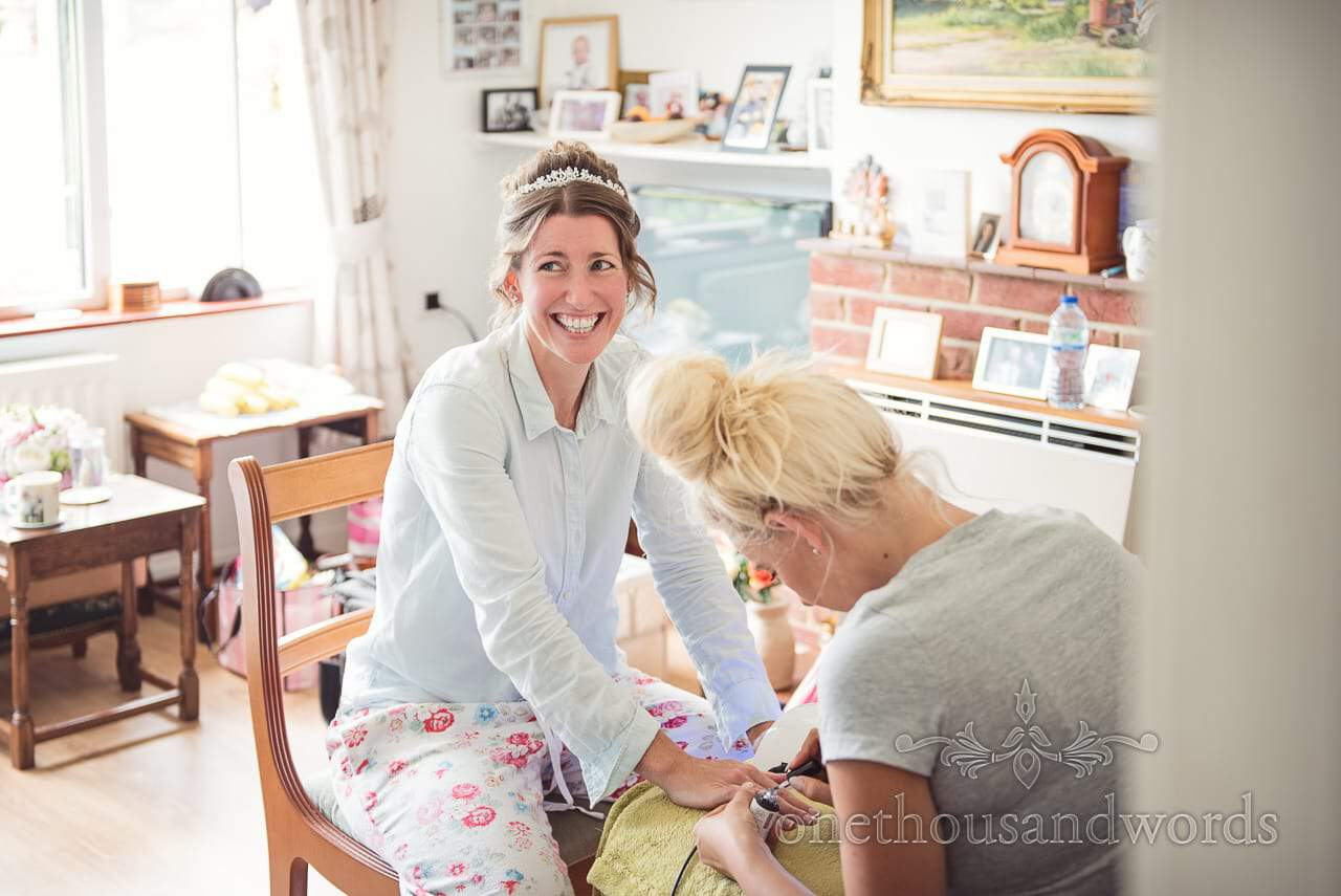 Bride in pyjamas has wedding nails done during wedding morning preparations