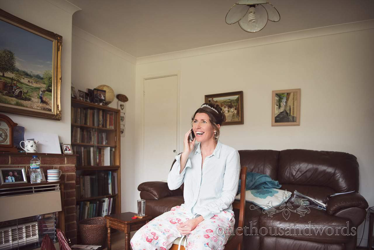 Bride in pyjamas laughs at phone call in parents living room on wedding morning