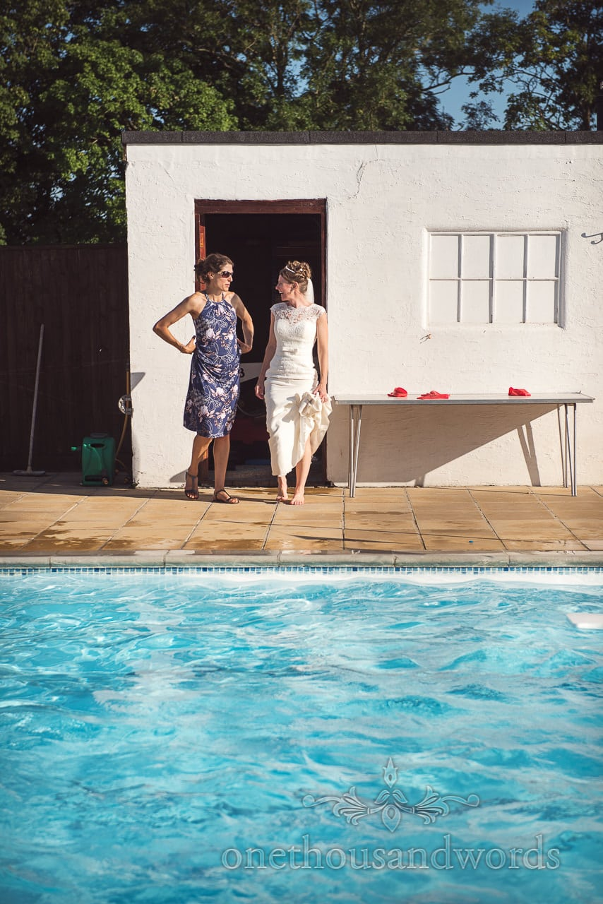 Bride in wedding dress and wedding guest next to swimming pool at Dorset wedding