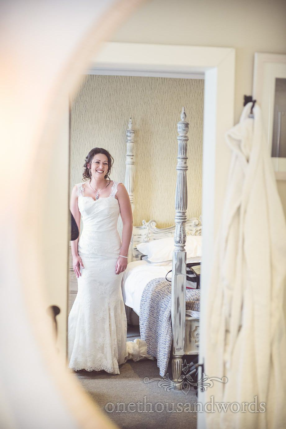 Bride in white trumpet wedding dress looks in full length mirror with white four poster bed