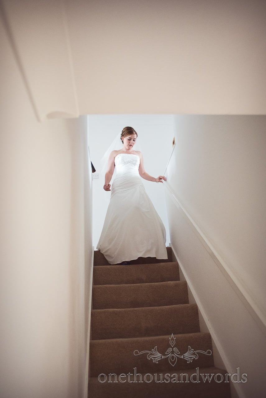 Bride in white wedding dress descends staircase at home on wedding morning