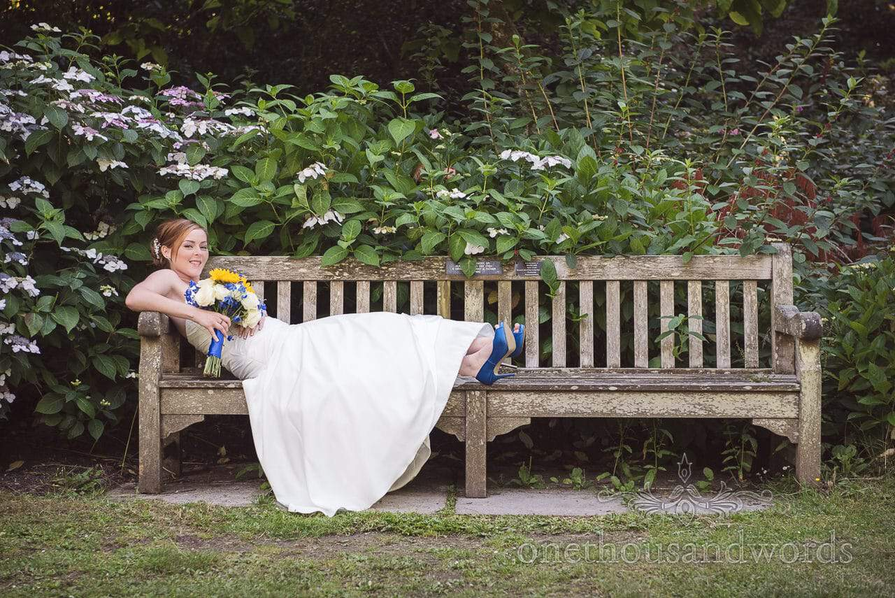 Bride in white wedding dress with blue shoes lying on wooden park bench at Upton House