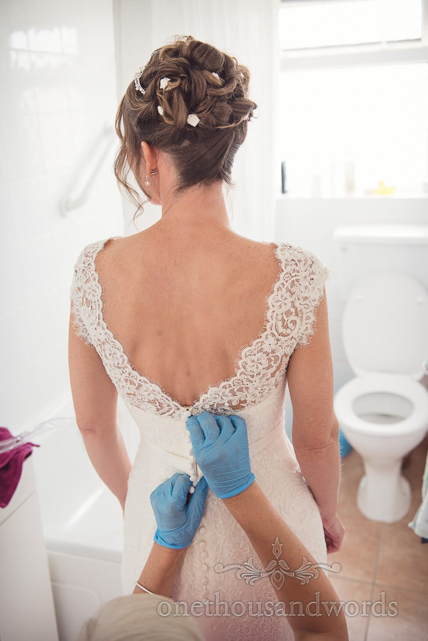 Bride is buttoned into lace detail white wedding dress by friend in blue gloves