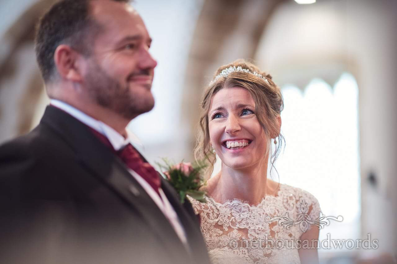Bride laughs at groom during white wedding church ceremony in Dorset
