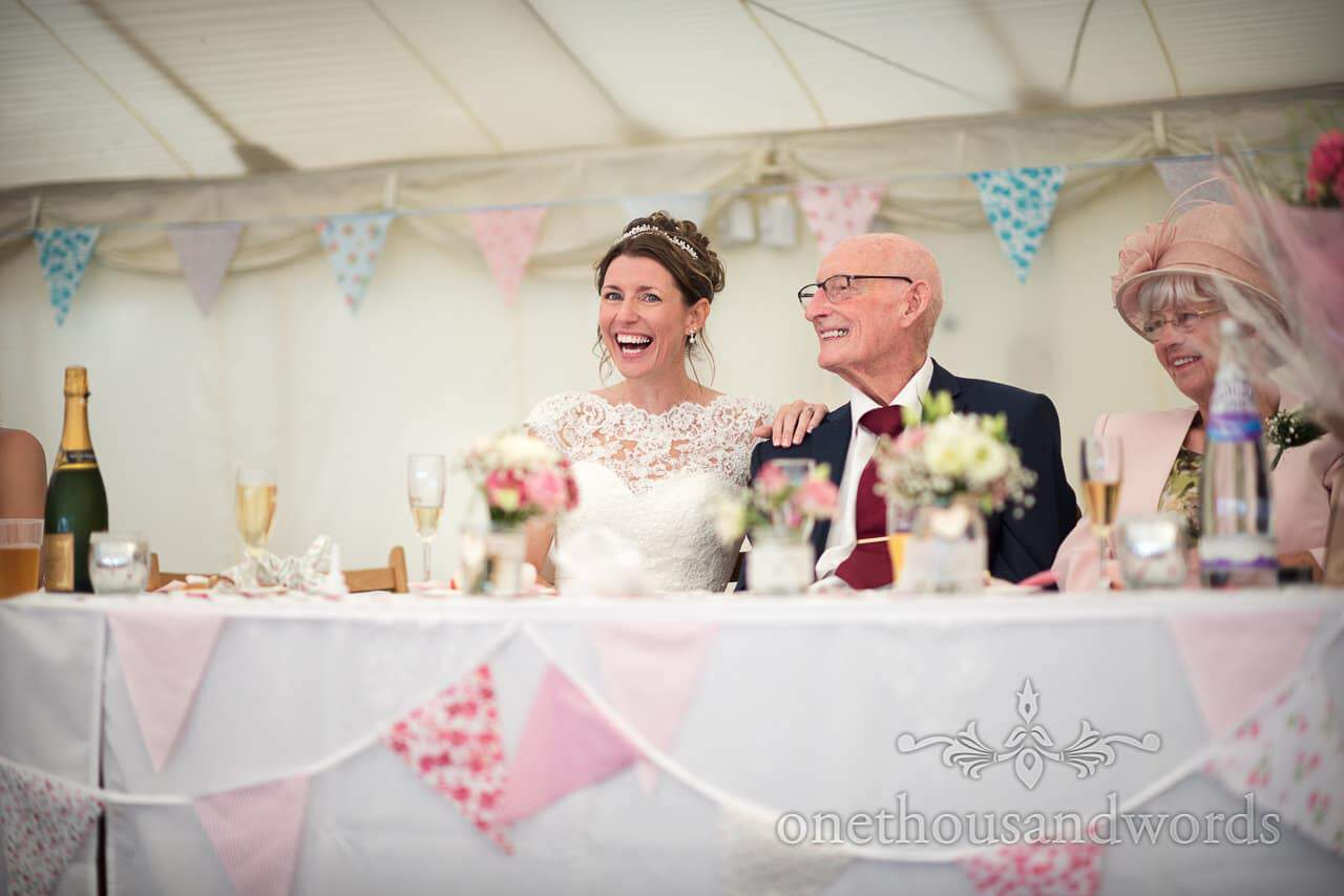 Bride laughs with her father under bunting at top table in marquee wedding