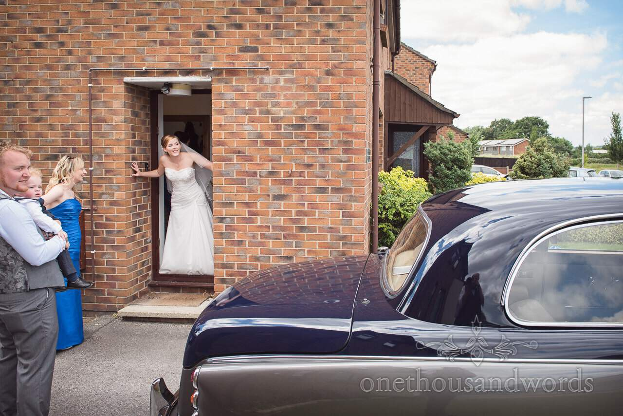 Bride looks out of red brick house at classic Daimler wedding car on wedding morning