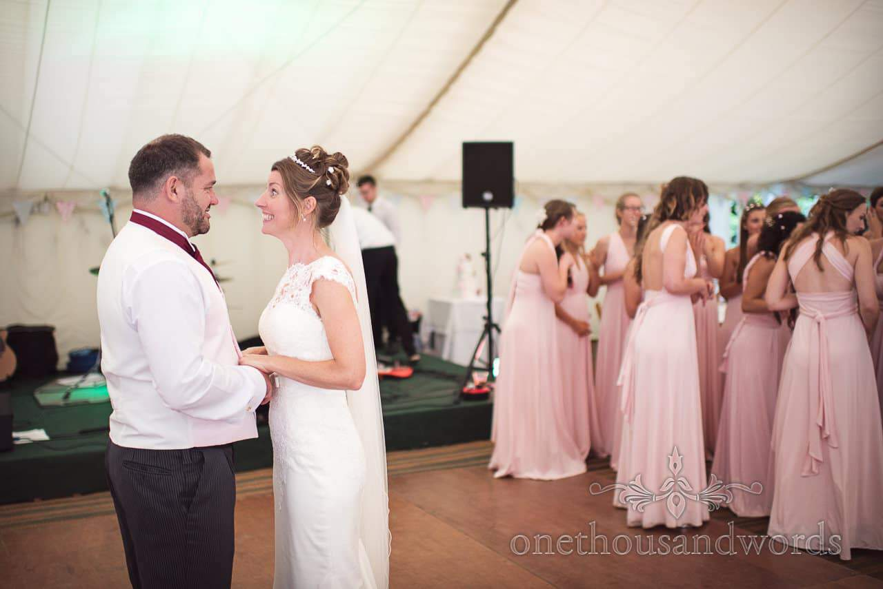 Bride pulls funny face at groom before first dance at country marquee wedding