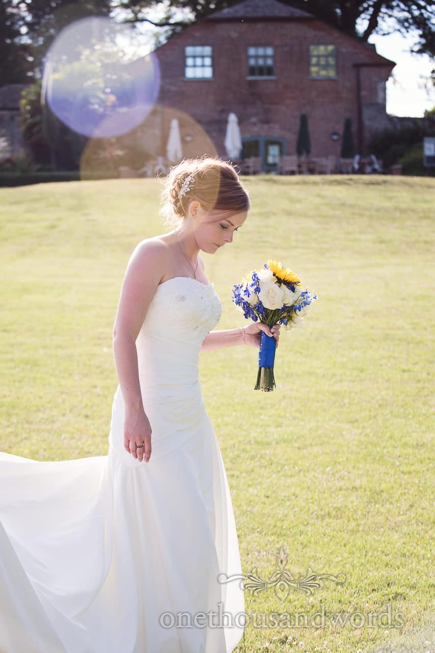 Bride walking through Upton House country gardens in summer sun with sunflower bouquet