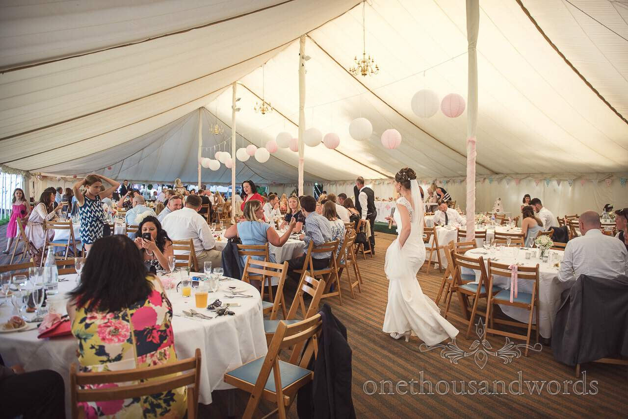 Bride walks through busy wedding marquee with Chinese lanterns and chandeliers