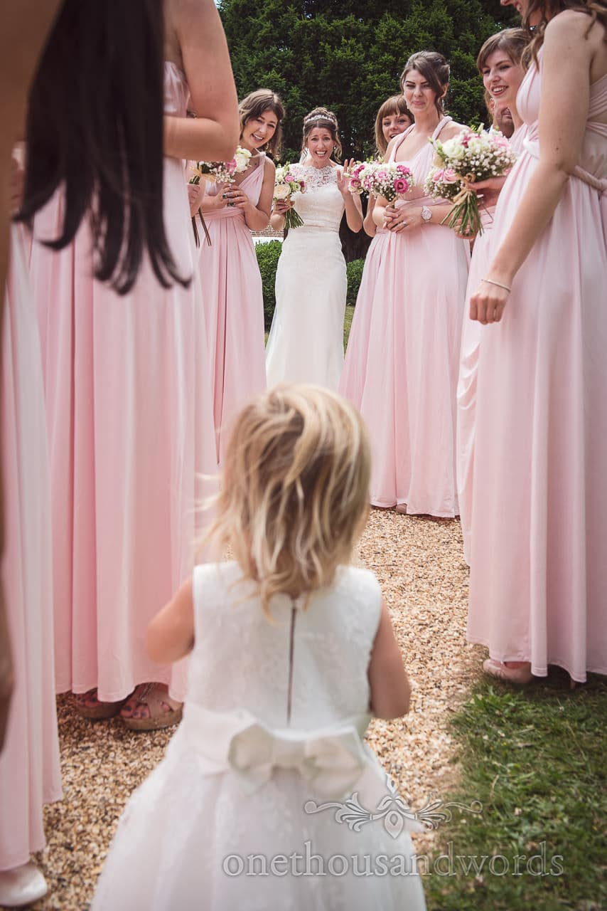 Bride waves at flower girl surrounded by group wearing pink bridesmaids dresses