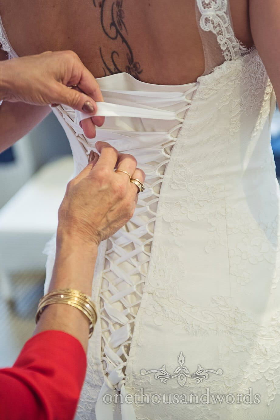 Bride with back tattoo is laced into white wedding dress by mother of brides hands