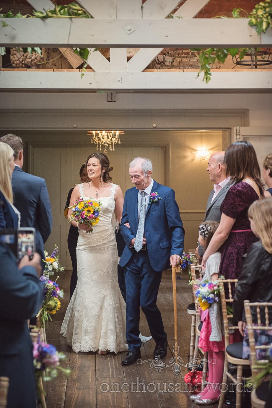 Bride with summer flowers bouquet walks down aisle at The Old Vicarage Wedding