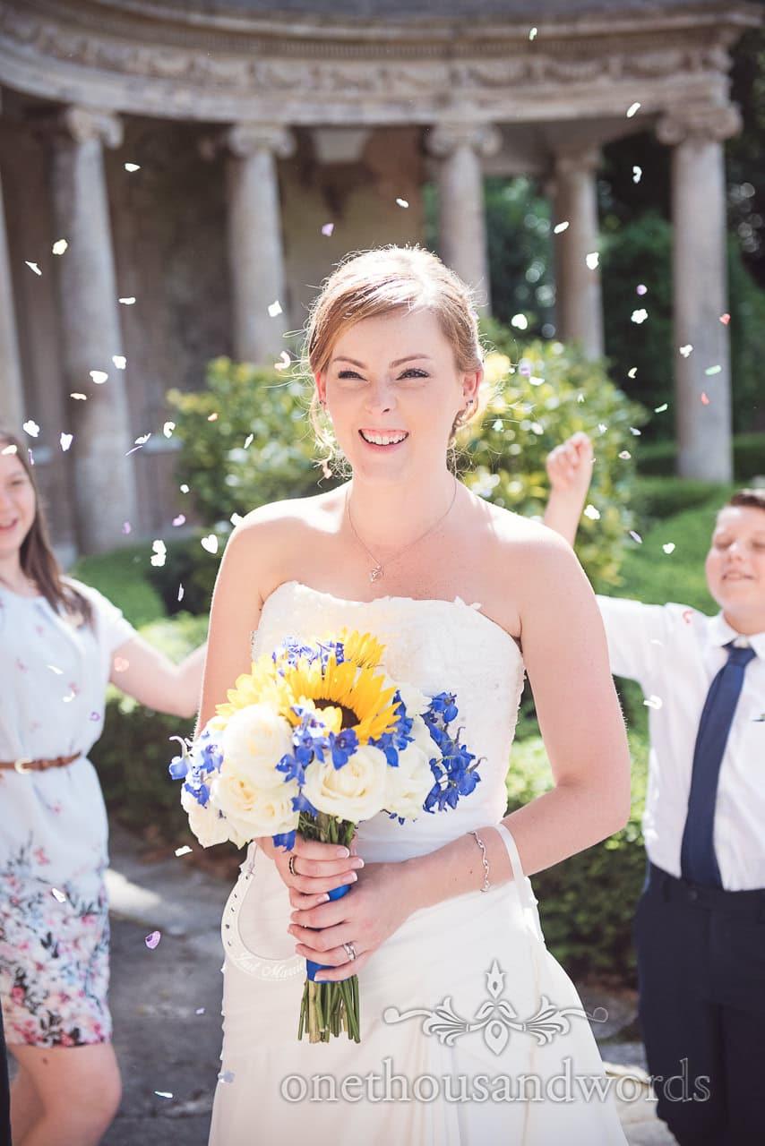 Bride with wedding confetti in the sun outside Upton House wedding venue in Dorset