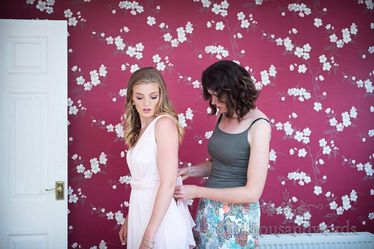 Bridesmaid has pink bridesmaid dress tied in front of red floral wall paper