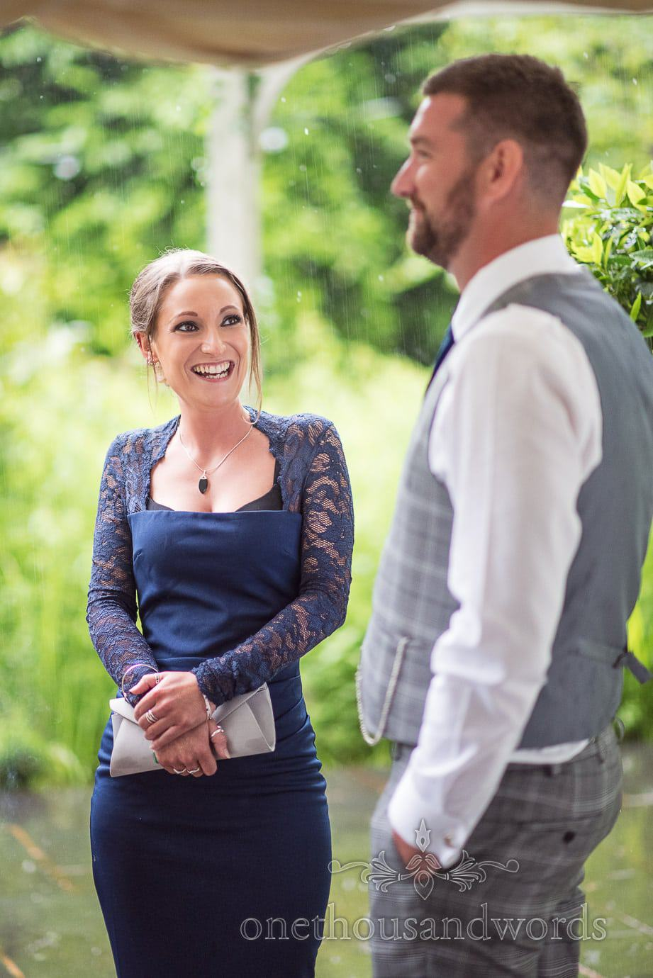 Bridesmaid in navy blue laughs at best man in the rain at The Old Vicarage Wedding