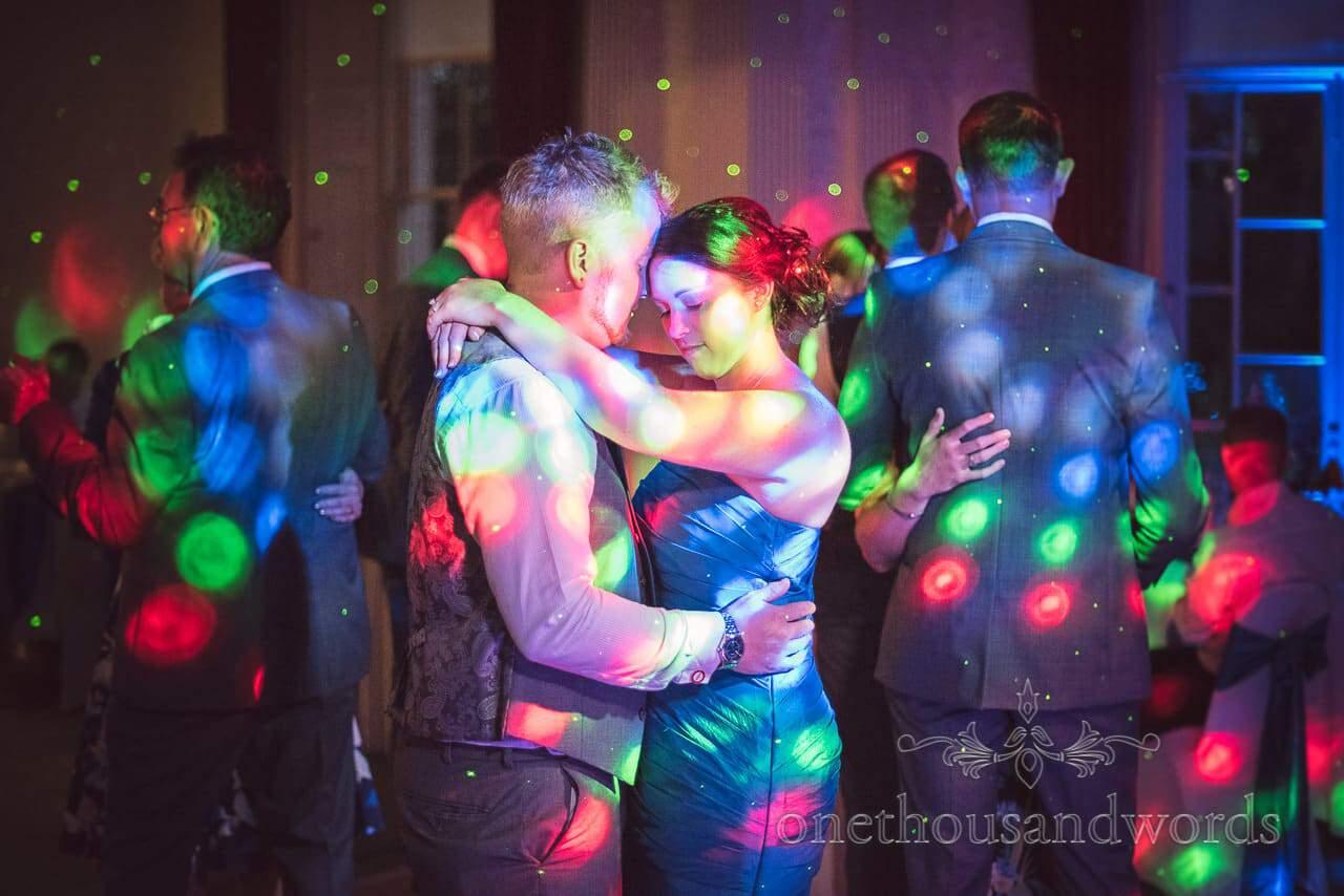 Bridesmaid romantic wedding dancing under multi coloured disco lights