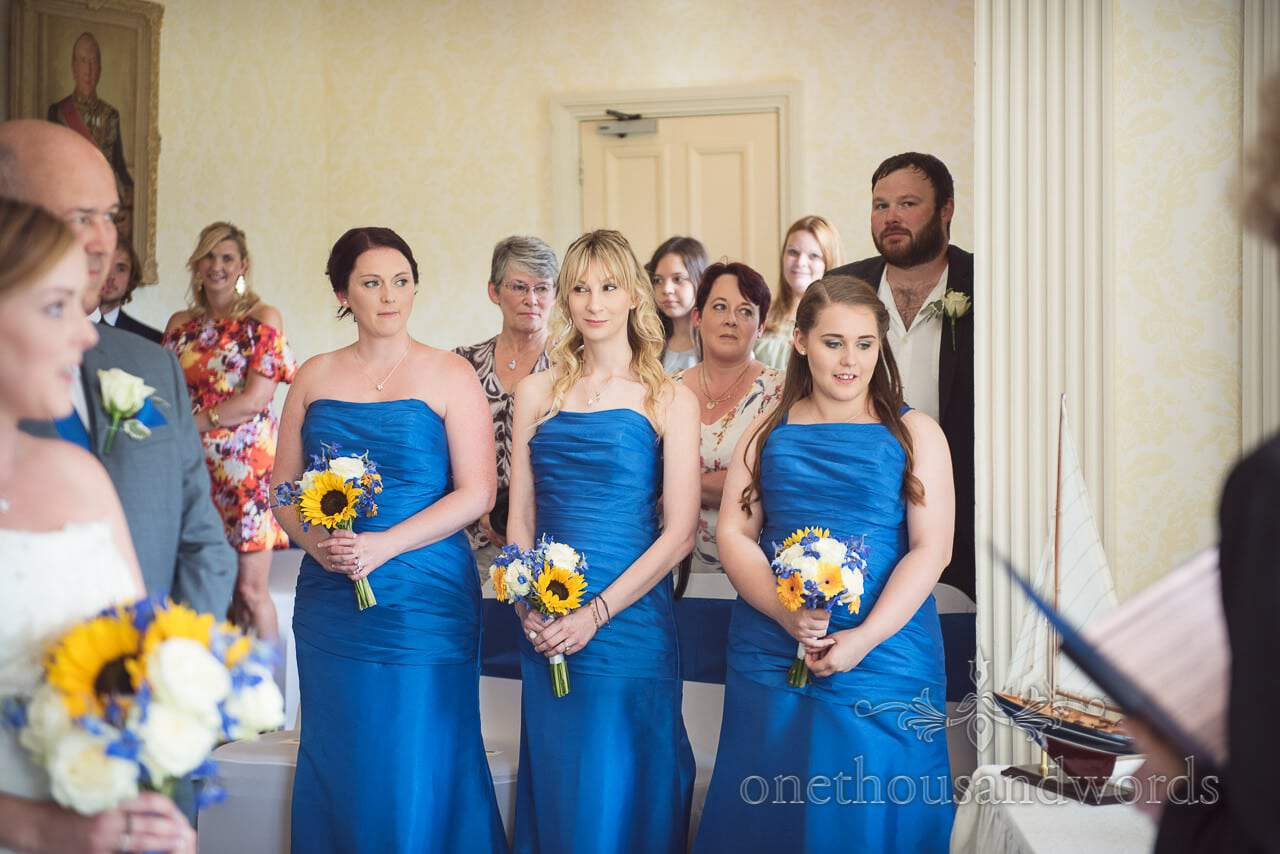 Bridesmaids in blue bridesmaids dresses with blue and yellow wedding bouquets