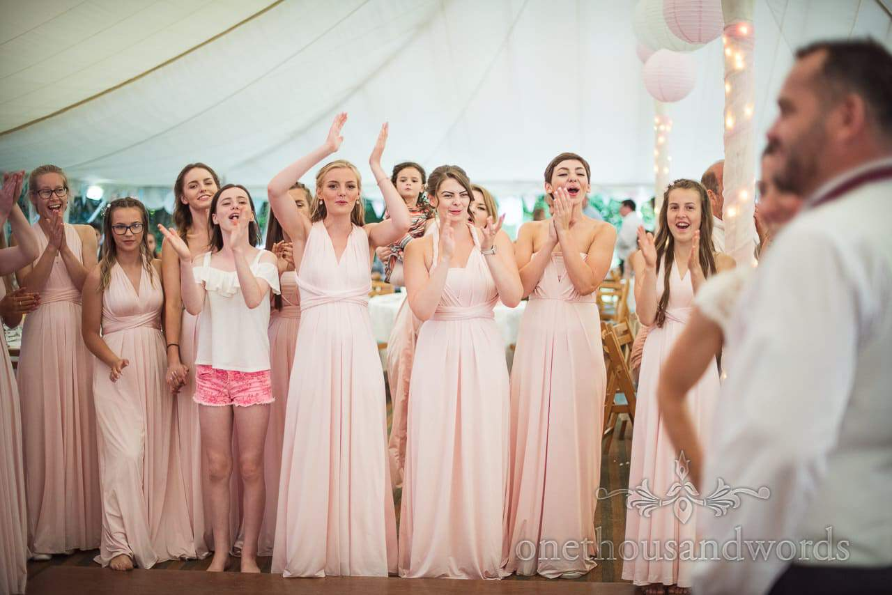 Bridesmaids in pink bridesmaids dresses cheer first dance in wedding marquee
