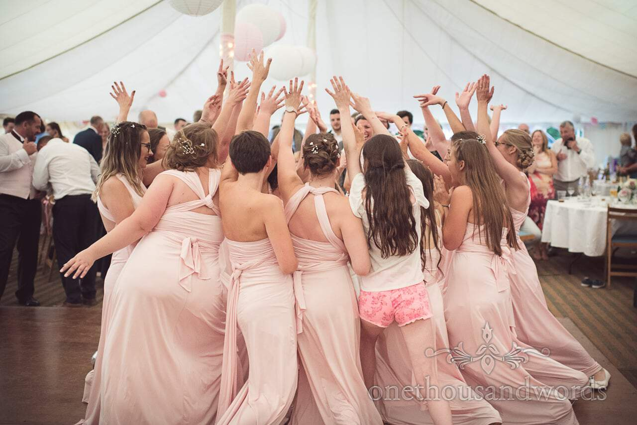 Bridesmaids in pink bridesmaids dresses dance in circle on marquee dance floor