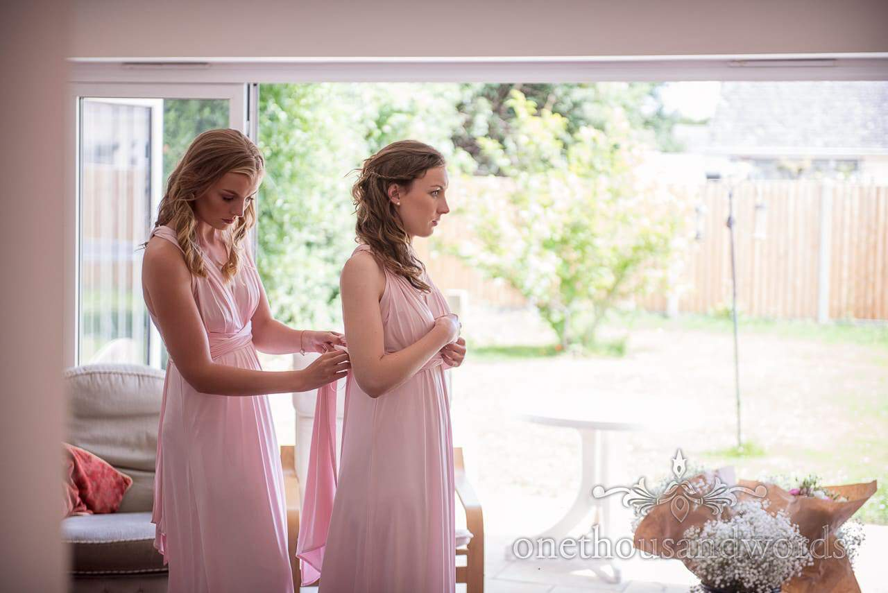 Bridesmaids tie each other into pink greco roman bridesmaids dresses on wedding morning