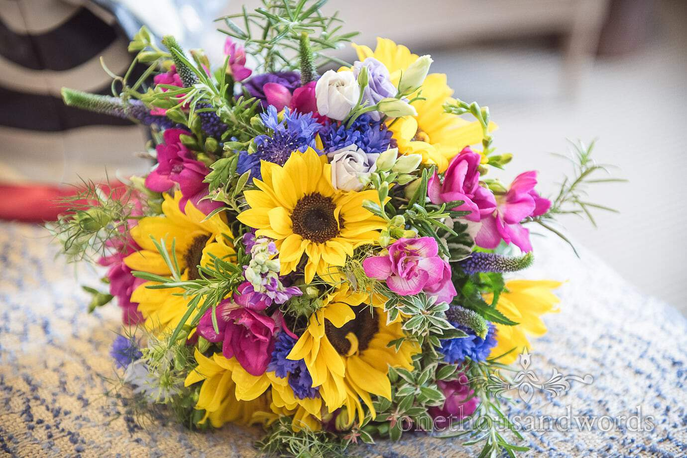 Bright countryside yellow pink and blue flowers wedding bouquet with sunflowers