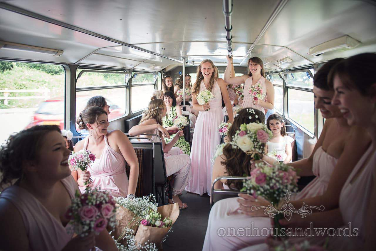 Bus full of bridesmaids in pink greco roman bridesmaids dresses driving to wedding