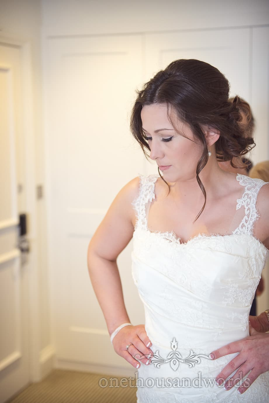 Calm bride portrait photograph as she is laced into wedding dress on wedding morning