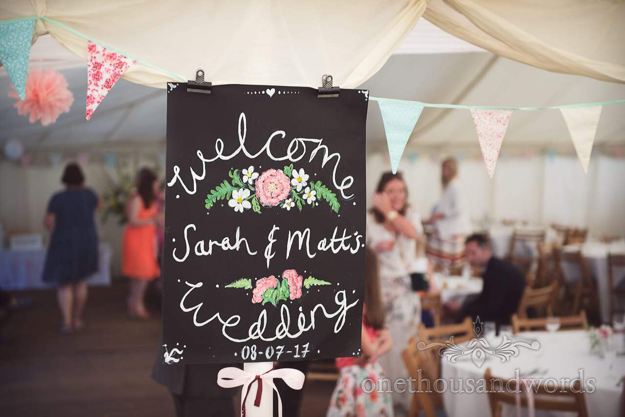 Chalk board wedding welcome sign with flowers hangs with bunting at marquee wedding