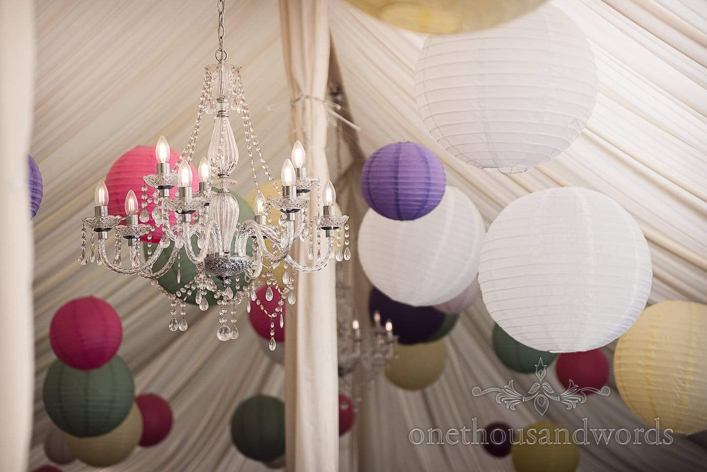 Chandelier and coloured Chinese lanterns in marquee roof at The Old Vicarage Wedding