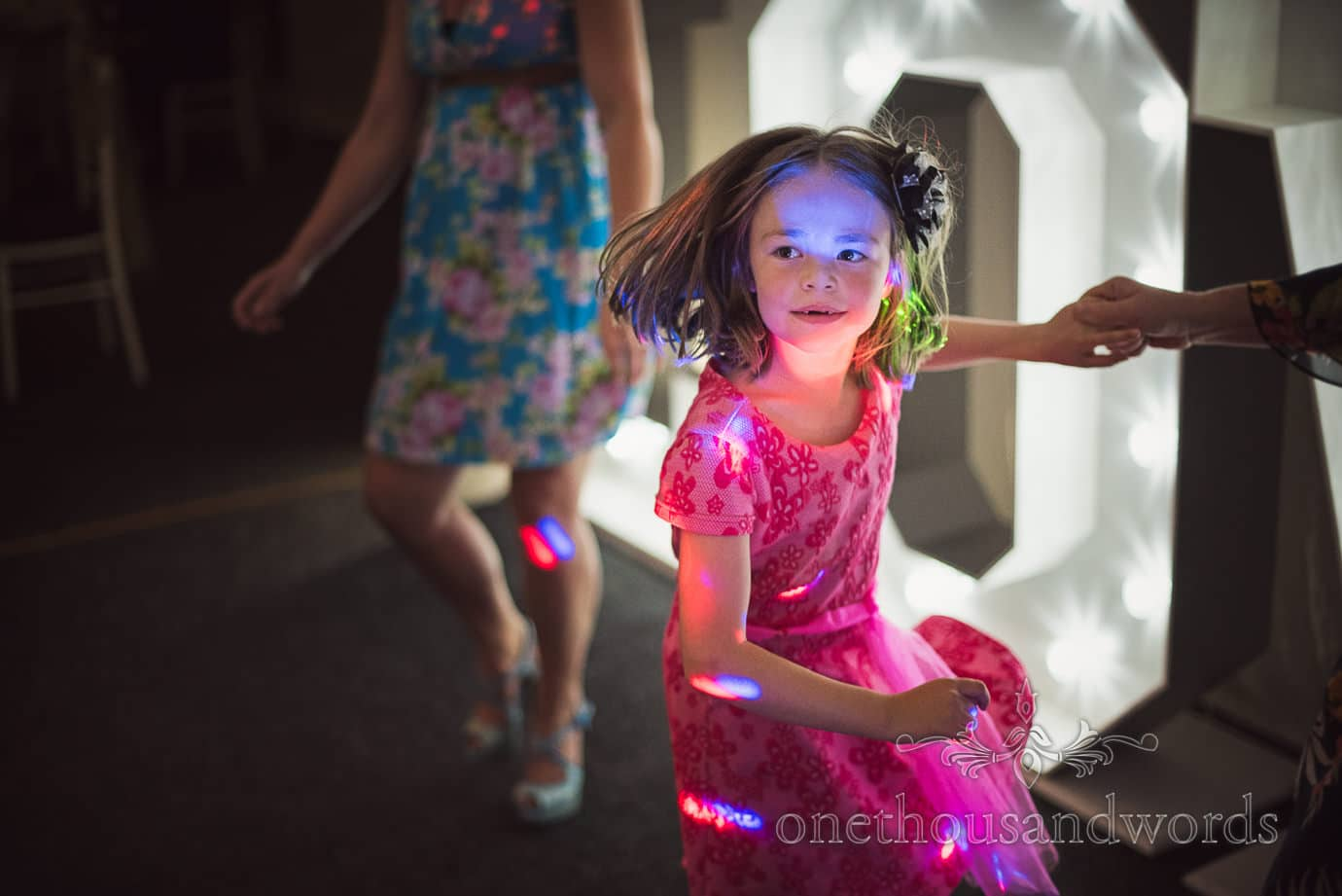Child wedding guest dancing in coloured disco lights at The Old Vicarage Wedding