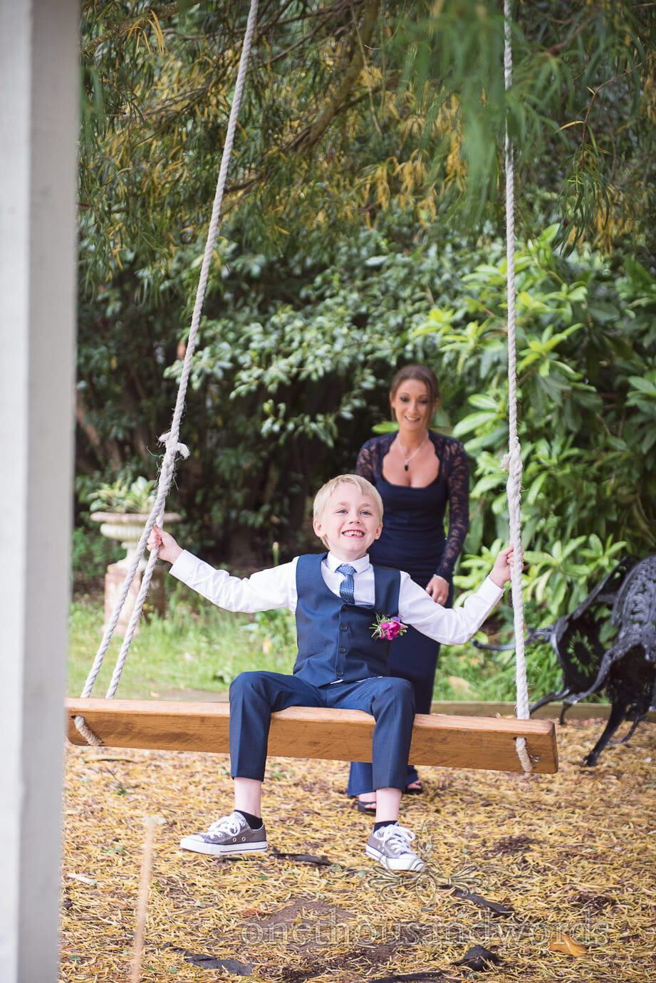 Child wedding guest is pushed on tree swing at The Old Vicarage Wedding venue